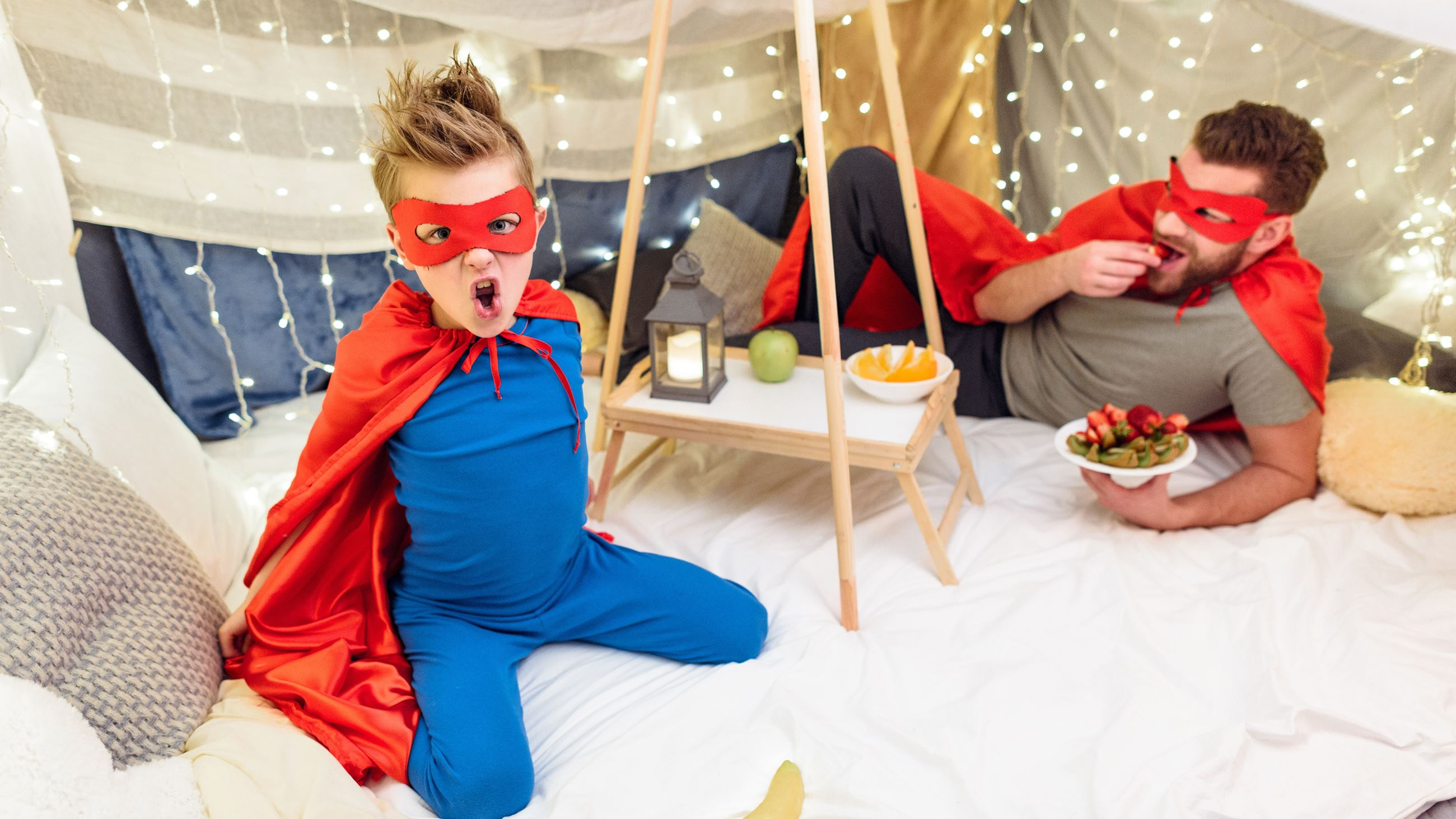 Happy father and son in superhero costumes eating fruits in blanket fort