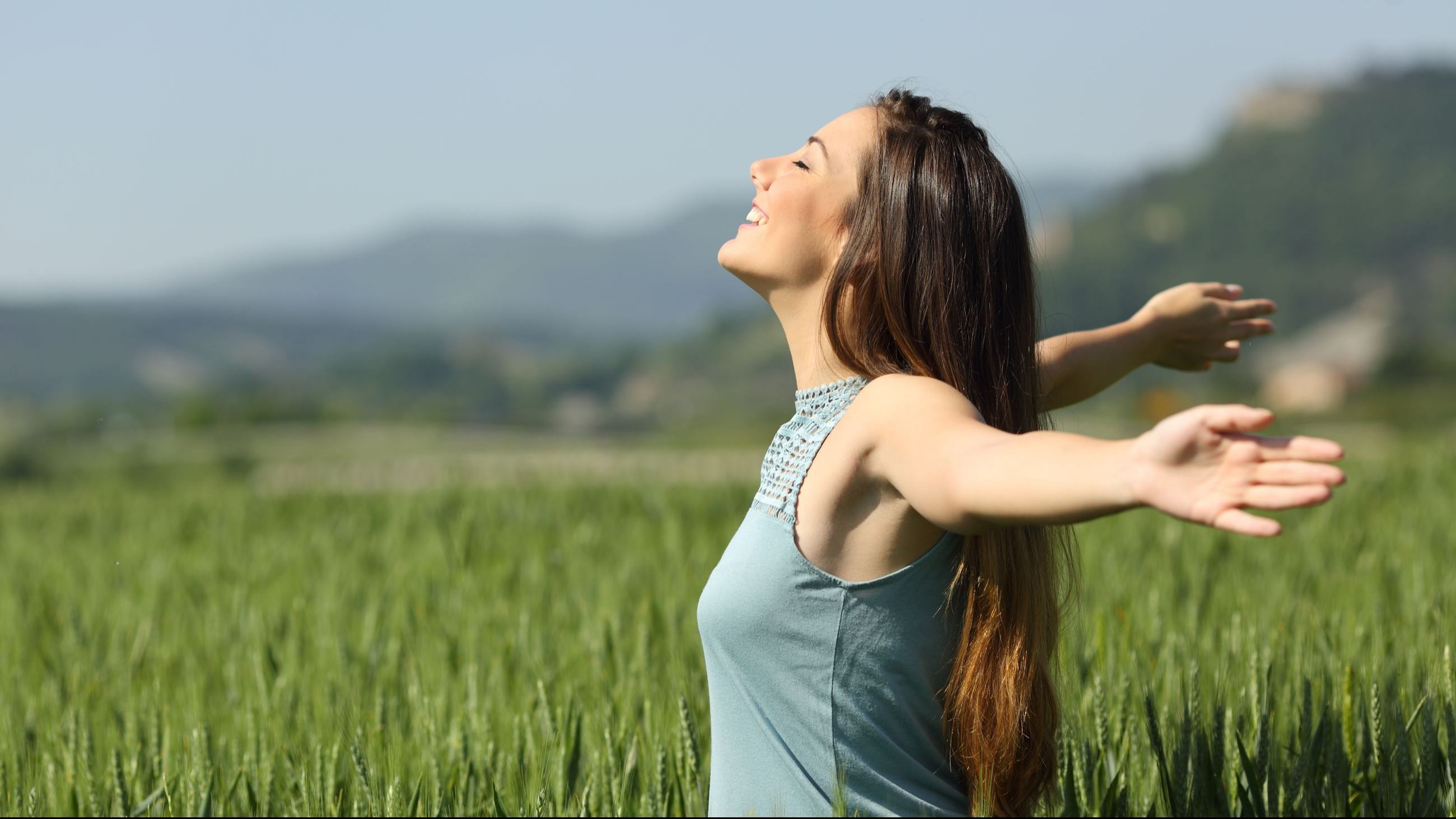 Happy woman breathing deeply fresh air in a field