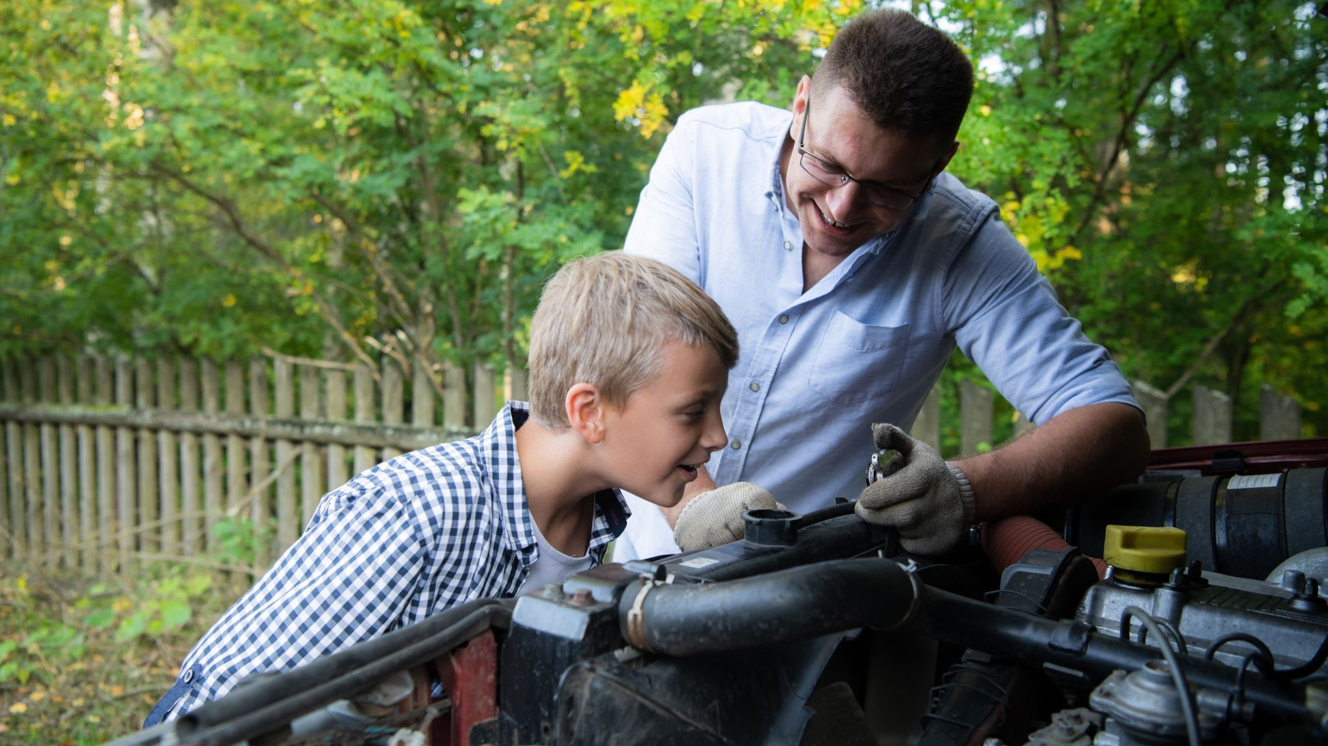 Dada and son working on a car AdobeStock_310192886